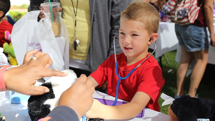 Child participates in animal clinic activity during Children's Day
