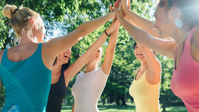 Women in exercise clothes do a group high five