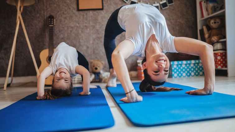 mom and daughter do yoga at home