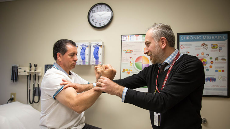 Male physician tests male patient's strength
