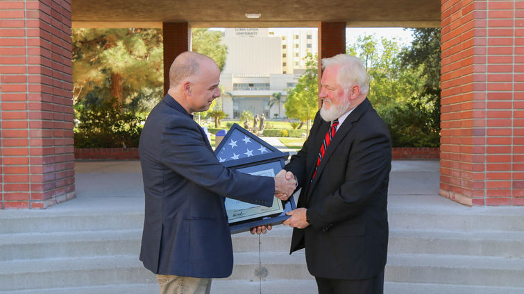 Two male professors shake hand over American flag