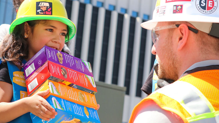 young girl scout holds colorful cookie boxes in front of kneeling construction worker