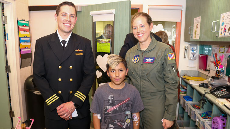 male and female pilot pose for photo with young male patient