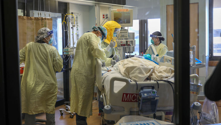 healthcare workers wearing masks and gowns caring for COVID-19 patient