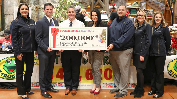 group of representatives stand with $200,000 check