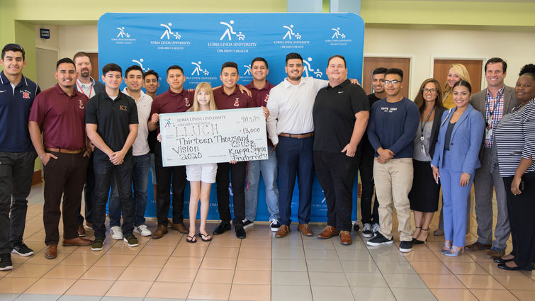 fraternity members stand with patient holding check