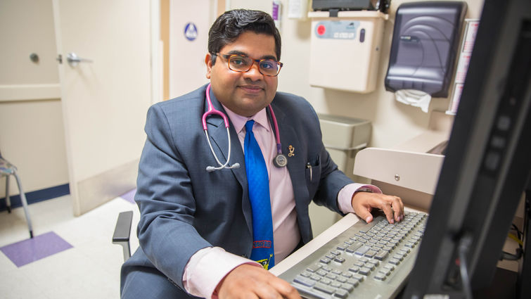 young indian doctor sits in front of computer