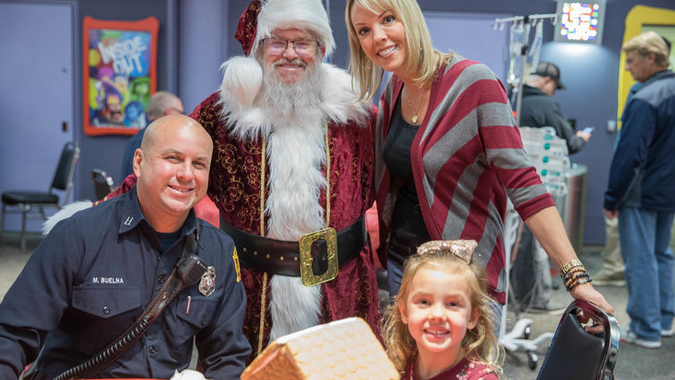 fireman, santa, mom, and kid pose for picture next to gingerbread house