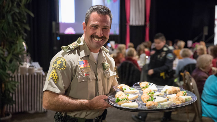 police officer holding tray of food for guests