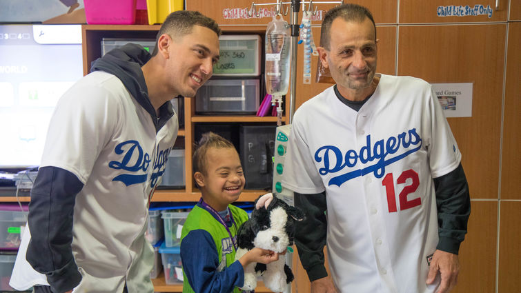 two baseball players pose for picture with young male patient