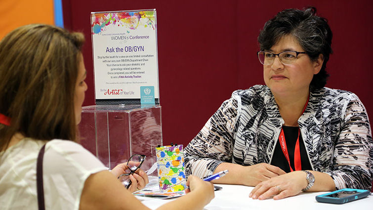 """A woman speaks with a doctor at the """"Ask the OB/GYN"""" booth at the Women's-Conference"""