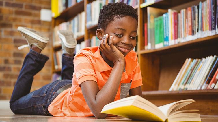 Boy reading on library floor