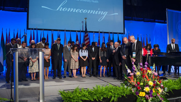Group photo of Homecoming attendees in prayer