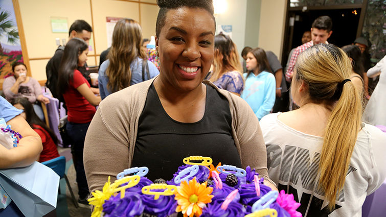 Woman holds cupcakes for special baby shower