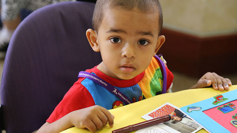 A patient from the Children's Hospital with book materials from the Fall into Reading event