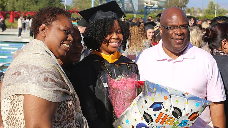Recent graduate poses for photo with loved ones