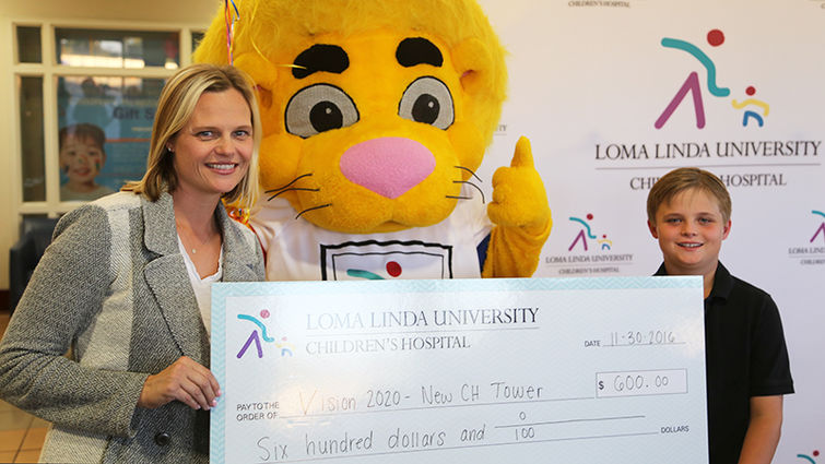 Max and Tammy Hilliard hold their check for Loma Linda University Children's Hospital.