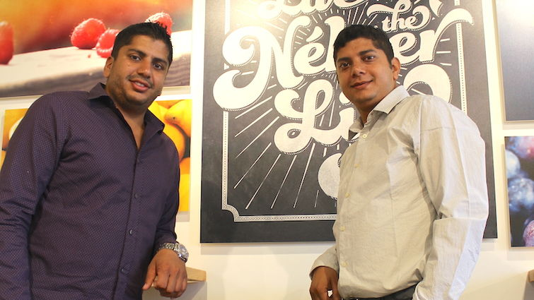 Batta brothers in front of a Nekter sign