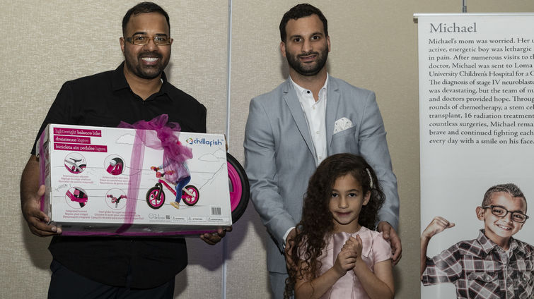 father stands with daughter while she is presented with bike