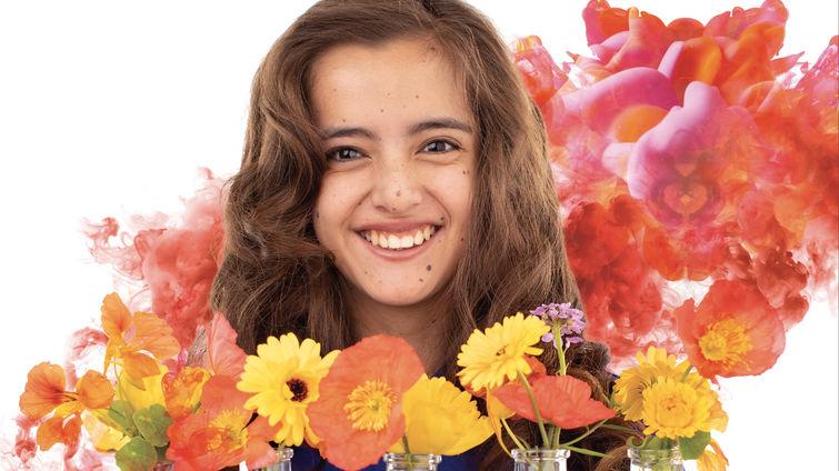 teenage caucasian female smiles in front of vases of flowers