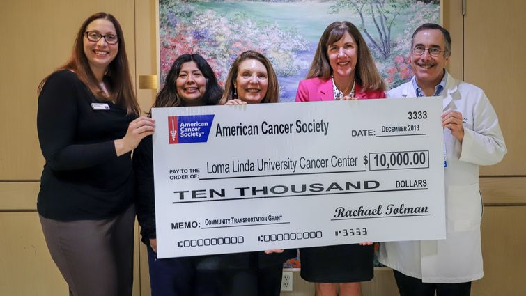 Five people hold giant presentation check