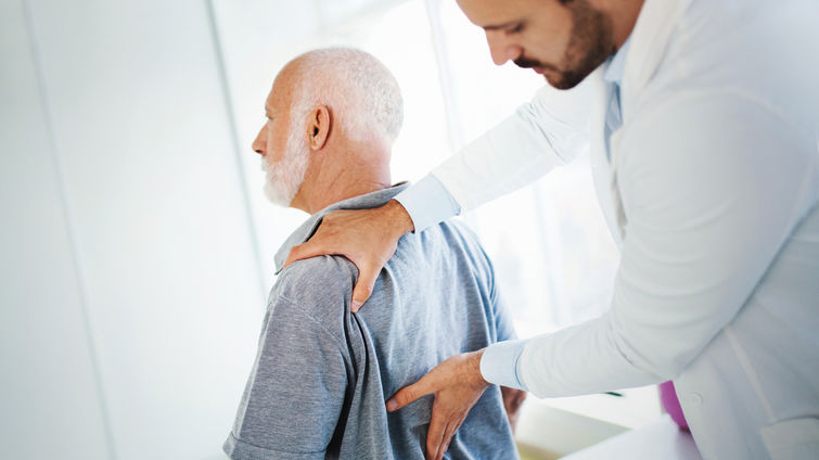 physician checks elderly mans back for pain