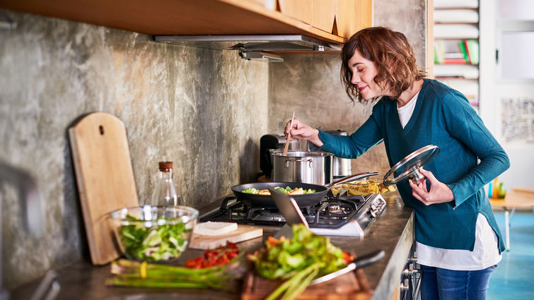 woman in the kitchen smelling her cooking food