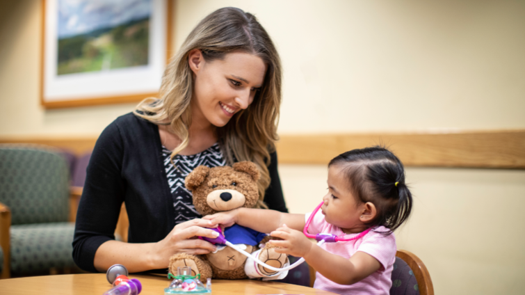 female child life specialists sits with patient who is playing doctor on a teddy-bear