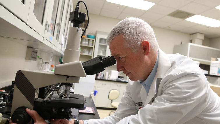 White male looking into a microscope inside a research lab