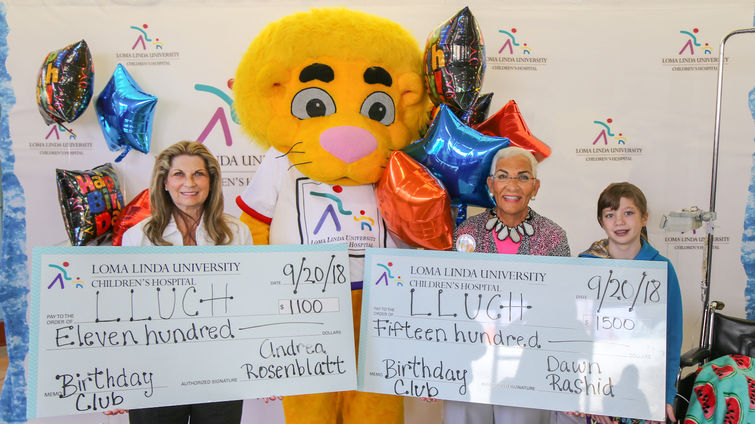 Andrea Rosenblatt (left) and Dawn Rashid presented their Birthday Club donation to LLUCH alongside Luke the Lion and LLUCH patient, Codi Pelton, 13, of Desert Hot Springs on Thursday, September 20.