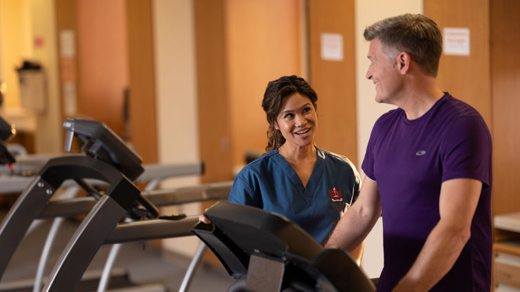 Healthcare provider observing patient walking on treadmill