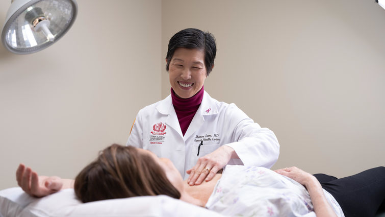 Dr. Lum performs a breast exam on a patient