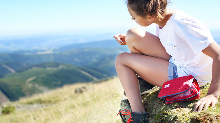 girl on hike puts band-aid on.
