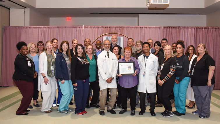 Group of doctors and staff stand in a large group holding an award