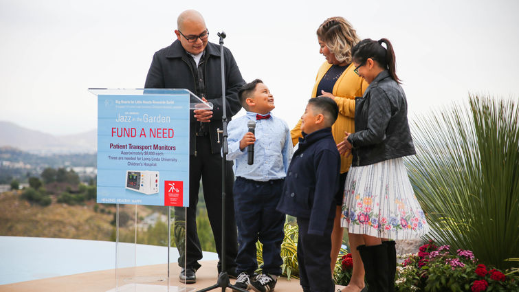 hispanic family stands together by glass podium