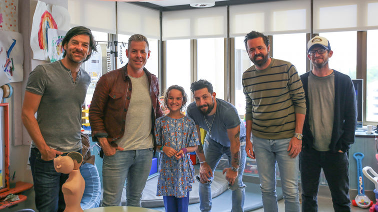 five members of country band poses with young female patient
