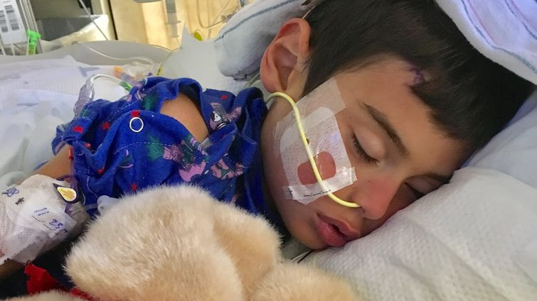 male pediatric patient sleeps in hospital bed with stuffed animal toy