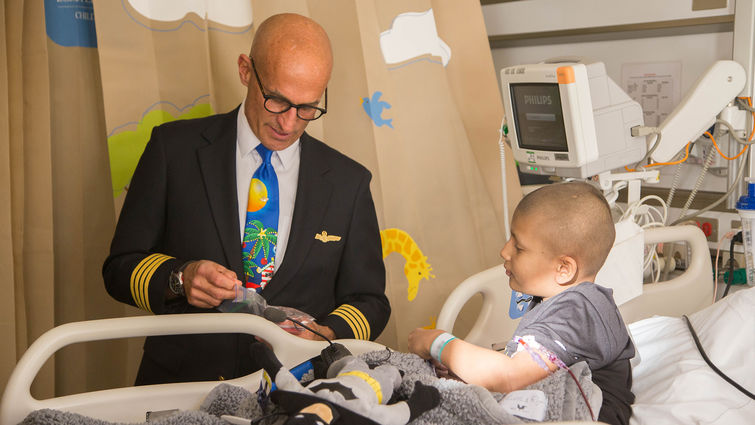 male pilot gives gifts to cancer patient