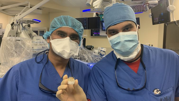 Cardiologists Harit Desai, MD and Niraj Parekh, MD and hold up an artificial heart valve used to replace diseased valves of patients during TAVR (transcatheter aortic valve replacement) procedures.