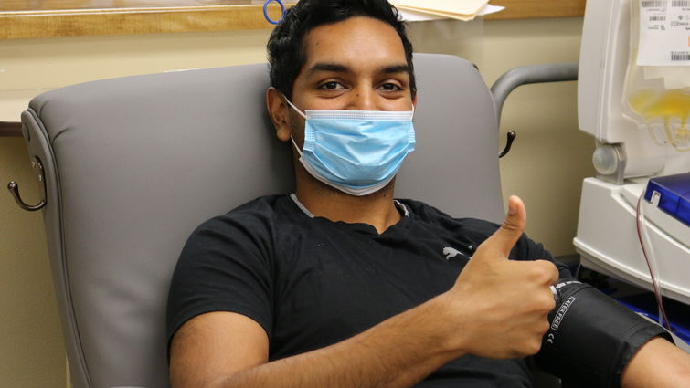 male sitting in chair giving blood