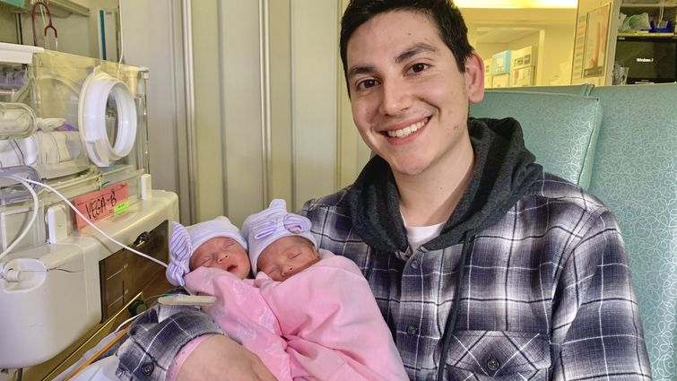 young father holds twin girls