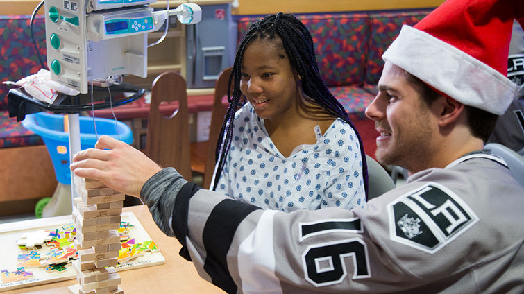 hockey player plays jenga with teenage female patient