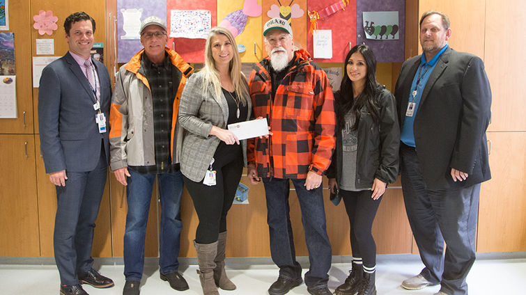 two male hospital administrators, one female Children's Hospital foundation representative, and three people from Quaid Harley-Davidson pose for photo with check