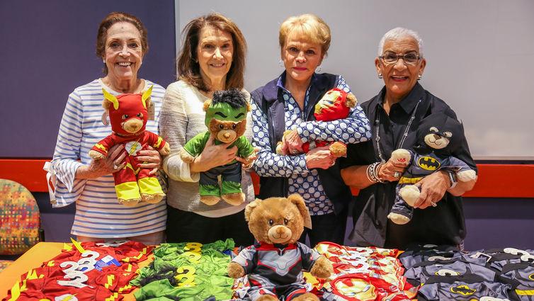 four elderly women holding teddy bears