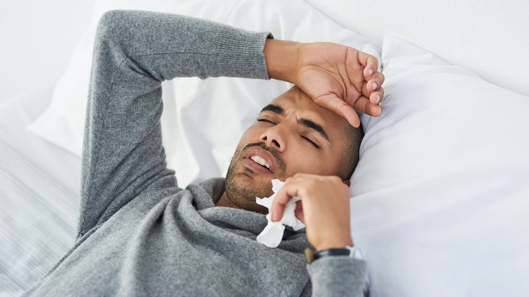 Man lying in bed with a headache