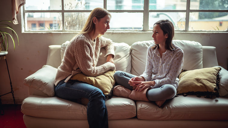 mother and daughter sitting on couch having a talk
