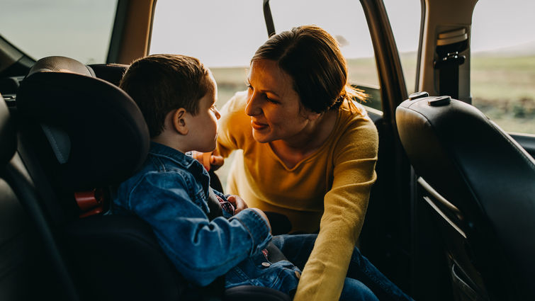 Mother talking to son in back of the car as she fixes car seat