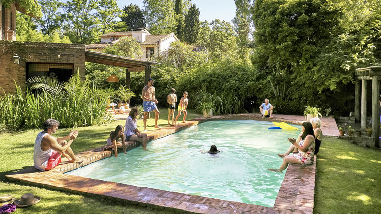 Wide angle view of multi-generation family relaxing and watching children play and swim in backyard pool