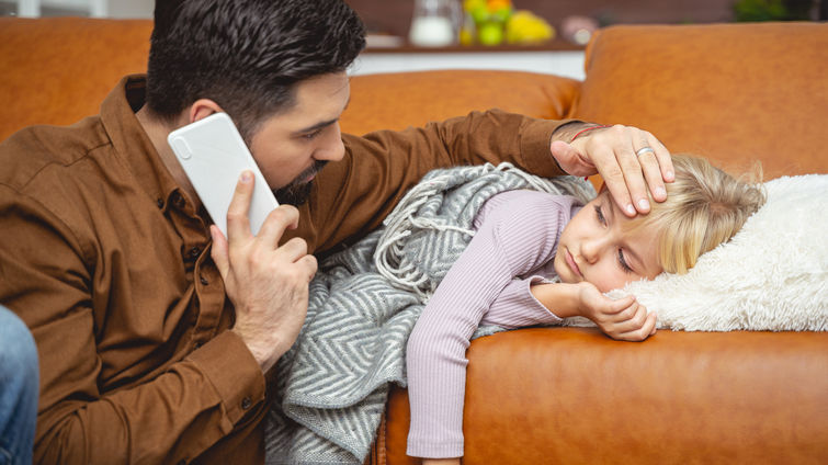 Caring father calling doctor and touching daughter forehead