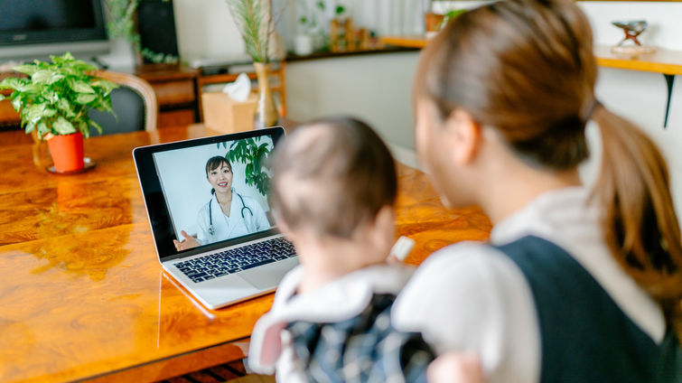 A mother with her baby is video calling a doctor on a laptop from home